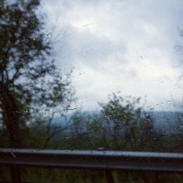 Looking out a car window with rain drops smeared across it with Pennsylvanian forest-covered hills in the back.