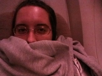 A picture o me in glasses in the plane with my hoodie wrapped around my mouth, neck, and shoulders.