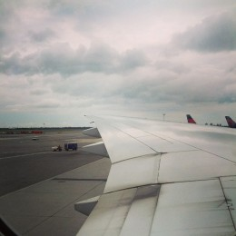 A picture of the plane's left wing and fluffy clouds in the background.